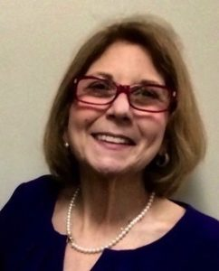 Image of Marcie Roth wearing Red glasses , head titilted, smiling.